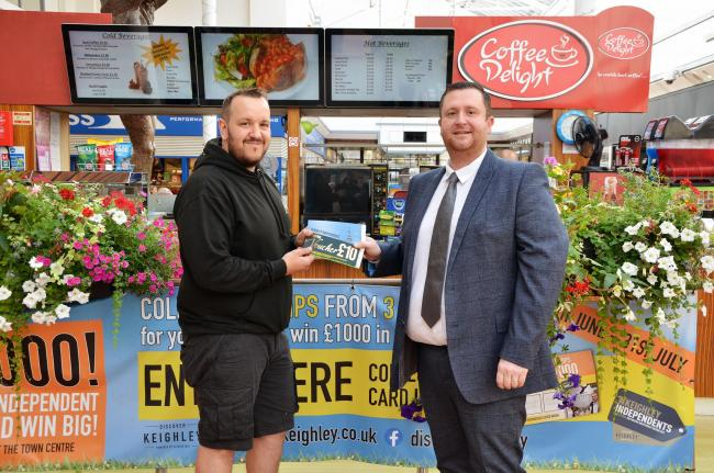 Competition winner Dean Muir, left, receives his vouchers from Keighley BID manager Paul Howard