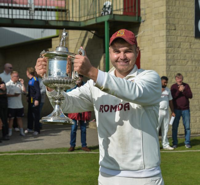Woodlands captain Cieran Garner with the Bradford Premier League Premier Division trophy last year. The team will not be playing in any of the league's revised competitions this year though. Picture: Ray Spencer