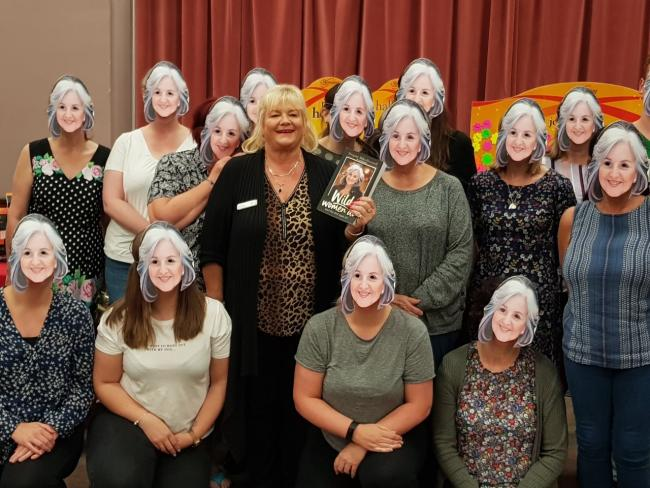 Andrea Astin, centre, with members sporting face masks of Slimming World founder and chairman Margaret Miles-Bramwell