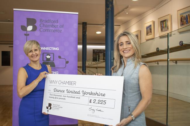 Suzanne Watson, left, presents a cheque to Helen Linsell