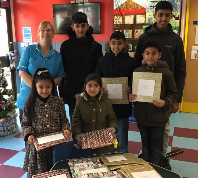 Youngsters from Ahmadiyya Muslim Youth Association present gifts at Airedale Hospital