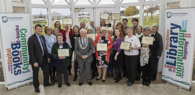 Libraries staff and volunteers receive their awards from County Councillor Jim Clark, with fellow councillor Greg White, left