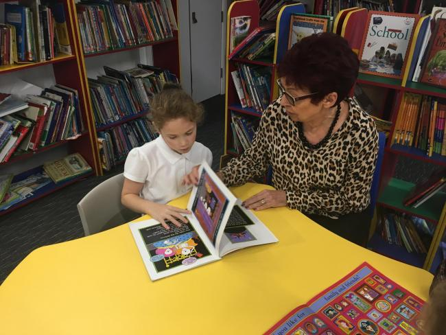 A child being supported by a Coram Beanstalk reading volunteer