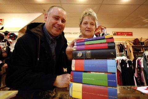 Michael Thompson hands over his Harry Potter book collection to British Heart Foundation shop volunteer Mavis Lonsdale