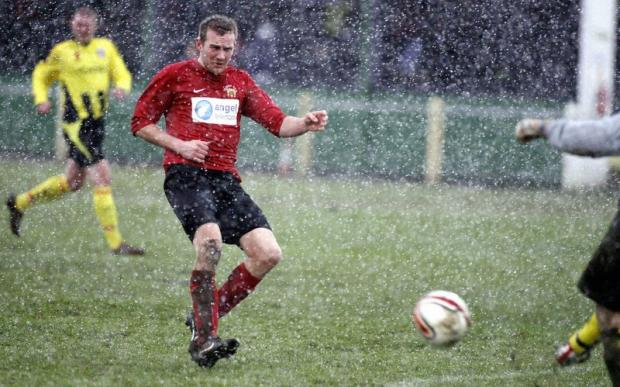 Silsden's Stephen Palfrey peers through a hailstorm as he puts pressure on Congleton's keeper