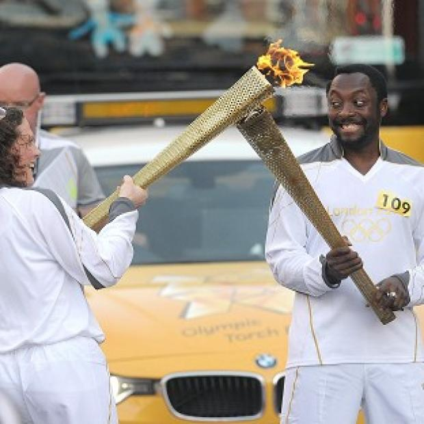will.i.am passes the Olympic Flame to torchbearer Emma Folwer in Taunton, Somerset
