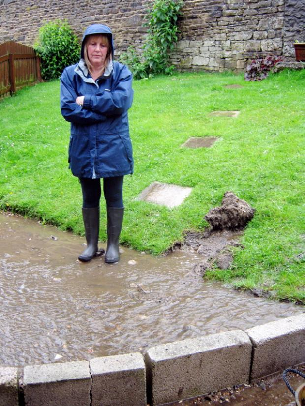 Julie Hastings in her flooded garden in Heritage Way, Oakworth