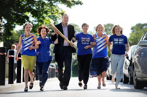 The Airedale Dodgers running club with Mike Farrar, centre, chief executive of the NHS confederation who is holding the Olympic torch he ran with through the village of Dalton during the build-up to the Olympics