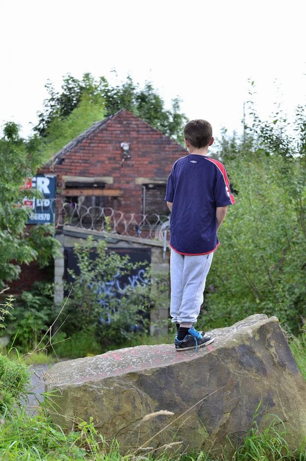 A young boy looks onto the disused mill by the side of Wirefield Road, Ingrow, where a teenager fell through the roof