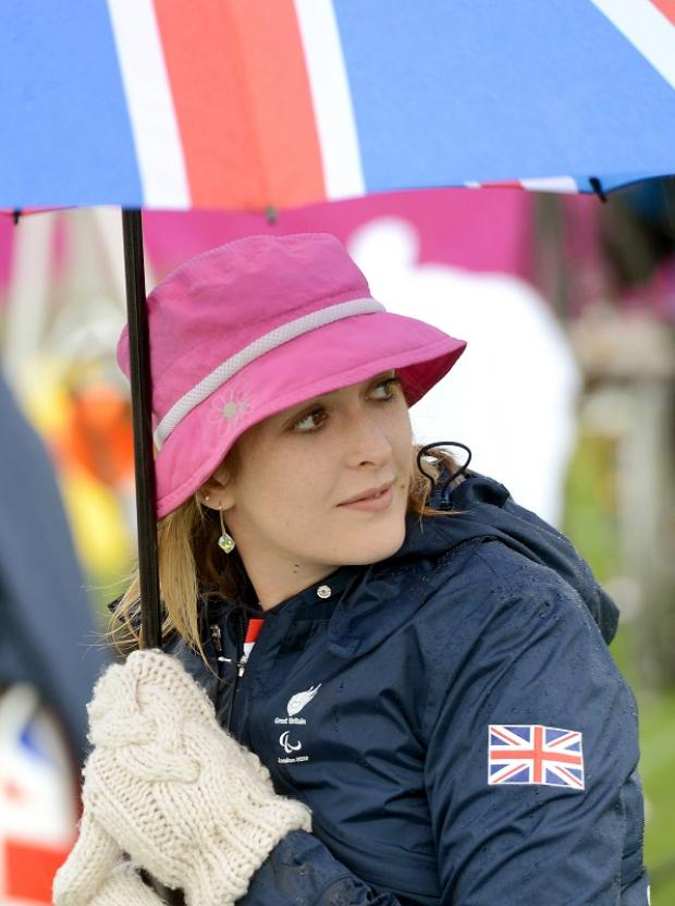 Danielle Brown takes shelter from the rain during the opening day of the Paralympics
