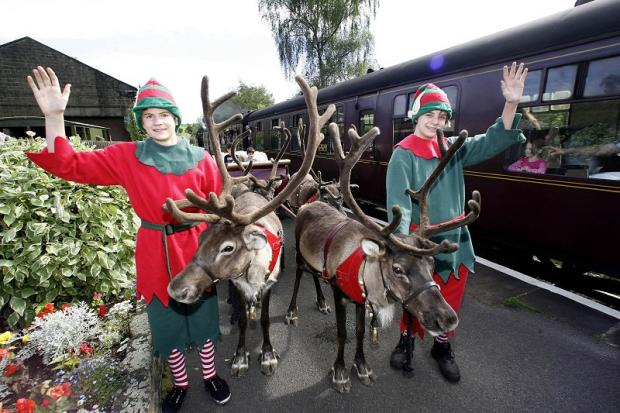 Santa's helpers Sid Ashworth, left, and Callum Porter take to the platform with reindeer at Oakworth to publicise the Keighley & Worth Valley Railway's Santa specials