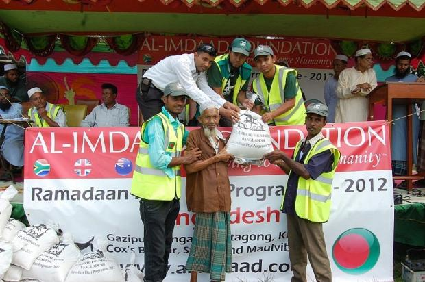 Keighley man Abdul Ahad (top centre) together with other charity team members giving an aid parcel to a Bangladeshi man