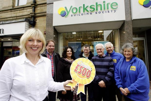 Keighley News: Yorkshire Building Society customer consultant Claire Kearns (left) with charity recipients (from left) Michael Cahill, Vicki Beere and Christopher Spencer, of Project 6; Michael Devlin of the Danny Ryan Memorial Fund; and two members of Cats Protection
