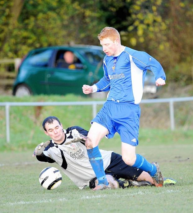 Grassington goalkeeper Robert Booth dives at the feet of Wibsey's Jamie Brannan