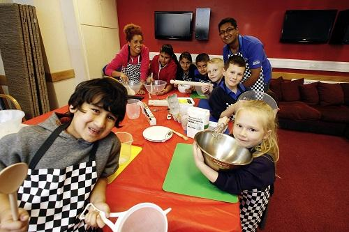 Play ranger Kelly Jordan and play ranger co-ordinator Hamid Miah join children as they prepare to bake biscuits