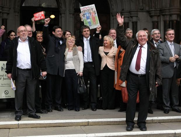 Trevor Hicks (front) waves as he comes out of the High Court in London, with other family members and supporters