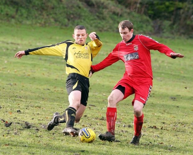 Grassington United's Billy Elliott and Andy North of Cross Hills challenge for the bal