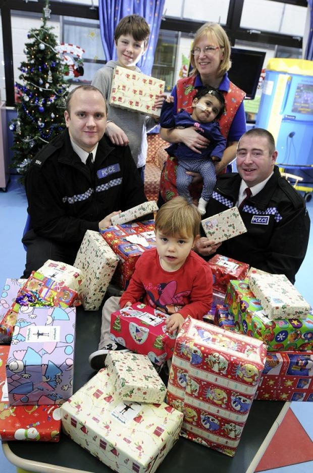 Police officers Ben Sutcliffe, left, and Gavin Hunter present gifts on Airedale Hospital children's ward to, back, Callum Wood, play assistant Karen Reece with Laaibah Ashraf, and, front, Scarlett Thake