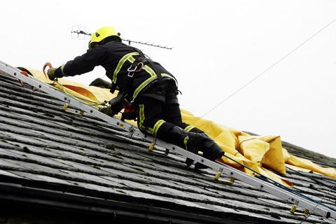 A firefighter makes the house roof safe