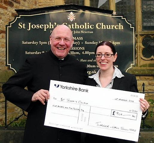 Melissa Murphy, of Turner & Wall, presents the proceeds of her bike ride to Father John Newman