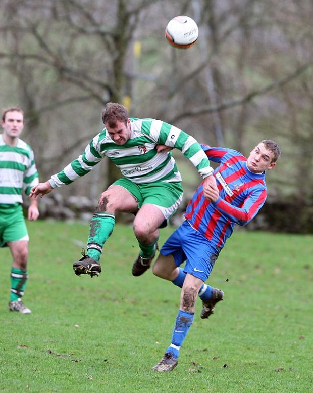 Grassington Reserves Graham Hunn wins a header during his side's 4-0 win over Cowling Reserves in Division Three