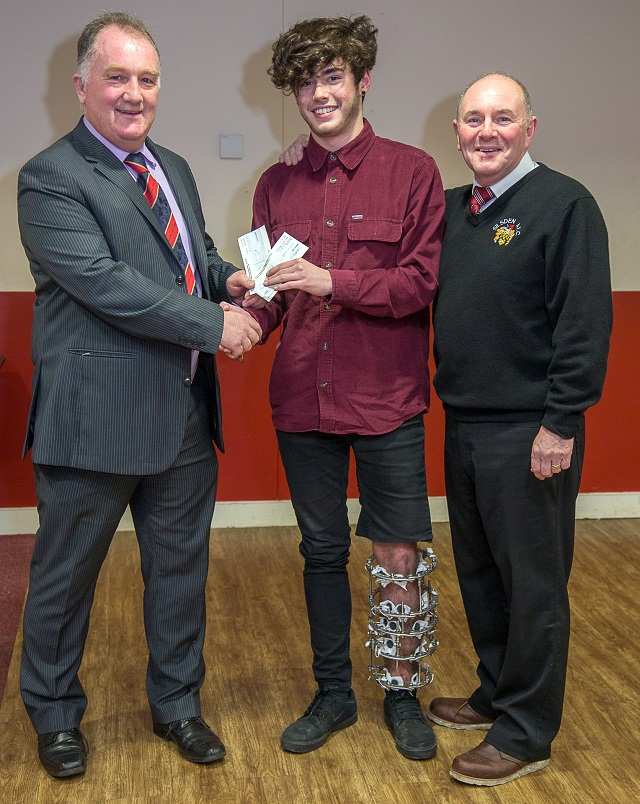 Oliver Simeone receiving £1,200 proceeds from the Silsden AFC benefit concert, before handing back half the money for the club to buy a life-saving defibrillator