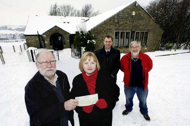 Oxenhope Community Association chairman Tony Maw, left, receives a £1,500 grant from councillors Rebecca Poulsen, Glen Miller and Russell Brown