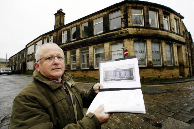 Ian Walkden displays a picture of the missing George Hattersley war memorial outside the former works in Heber Street, Keighley
