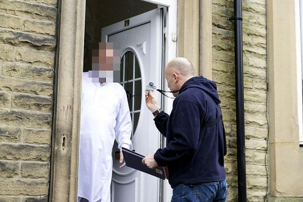 Police serve an injunction at a house in Keighley during the operation targeting gang activity