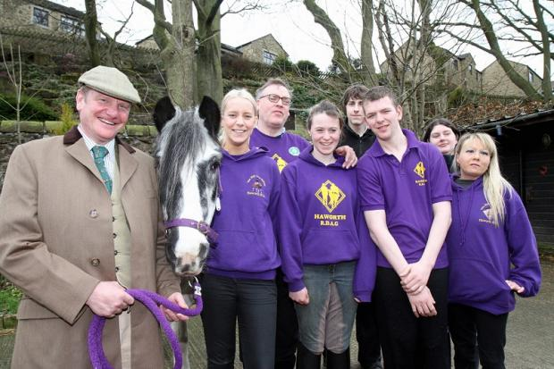 Sovereign Health Care chairman, Michael Bower, left, joins Haworth Riding for the Disabled's Laura Bland, second left, with volunteers at the charity, which received £10,000 from the health group