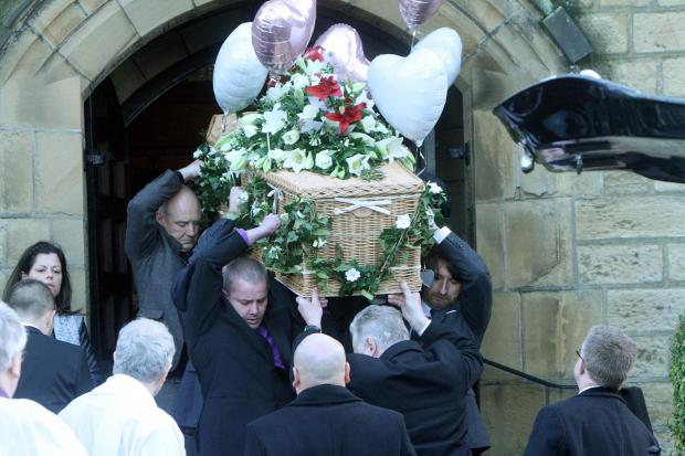 The coffin leaves the church after the service