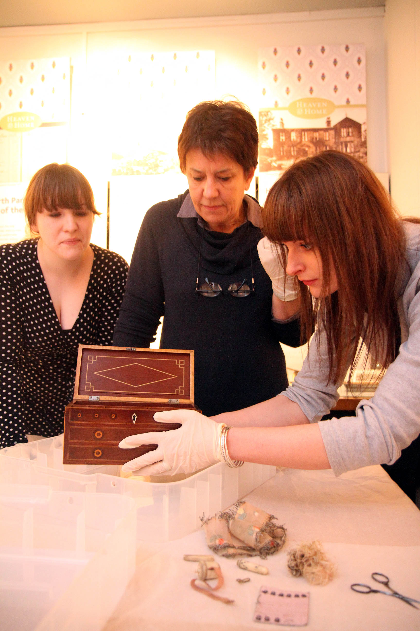Bronte Parsonage library and information officer, Sarah Laycock, right, puts away a sewing box that belonged to the literary sisters, watched by volunteer steward, Amy Rowbottom, left, and museum assistant, Linda Pierson