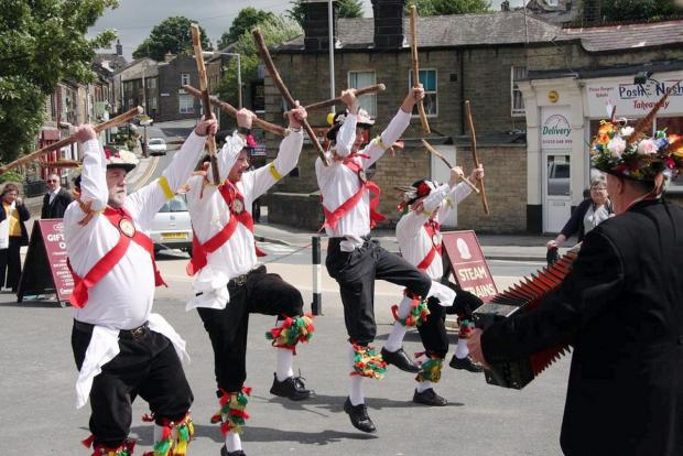 Keighley News: Performing last summer are members of Oakworth Village Morris Men, who are making an appeal for new members to attend a try-out