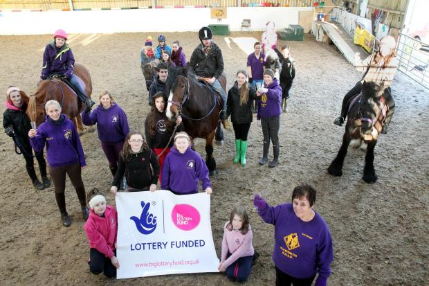 Keighley News: Jackie Butterfield, front right, joins staff, volunteers and users to celebrate the National Lottery grant