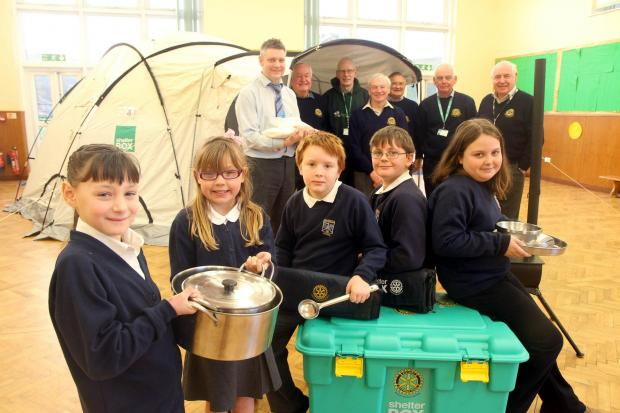 Glusburn Primary School headteacher, Richard Hunt, back left, joins pupils and Skipton Rotary members with the Shelterbox equipment