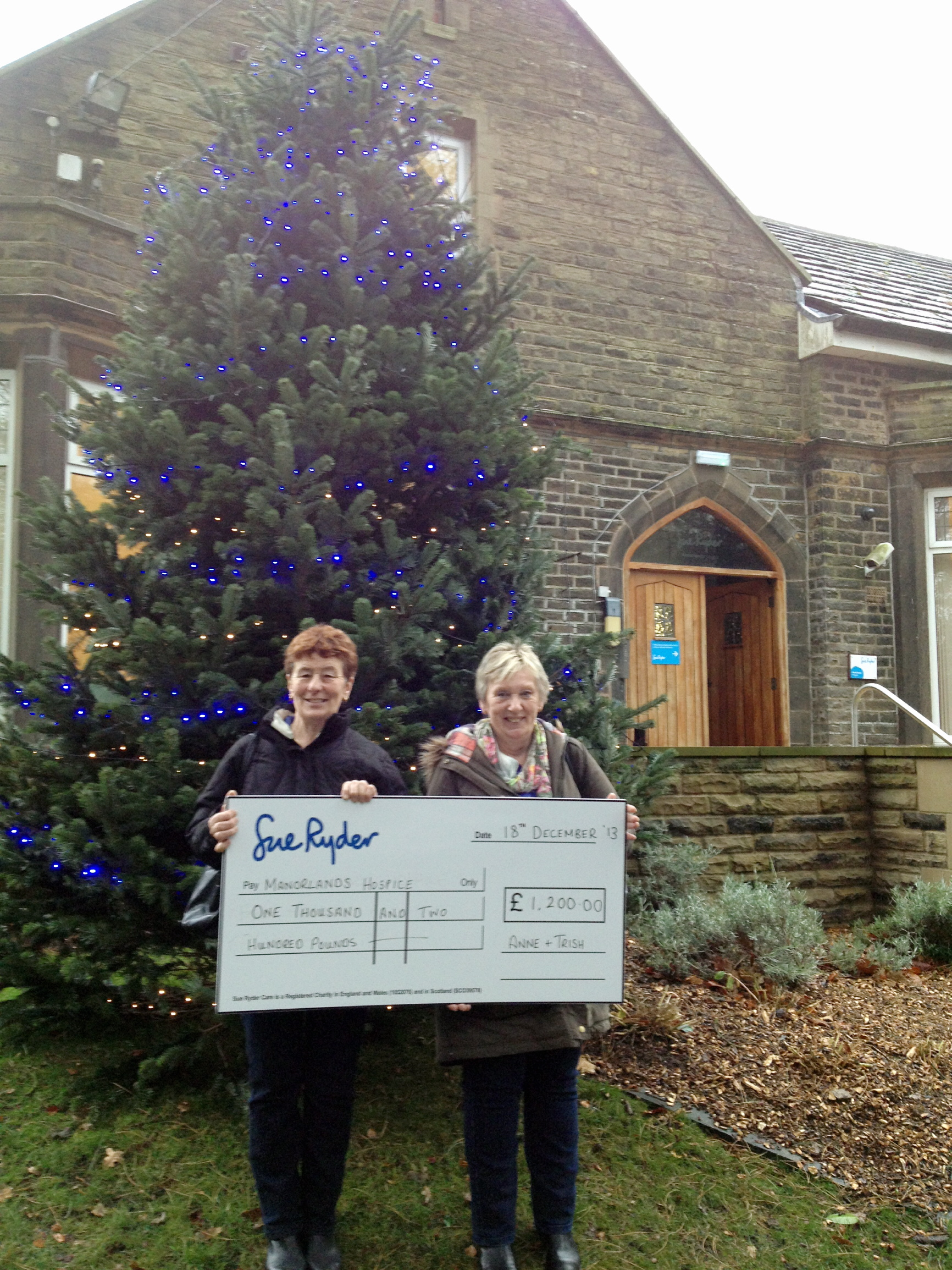 Anne Thompson, left, and Trish Wood present a cheque outside Manorlands