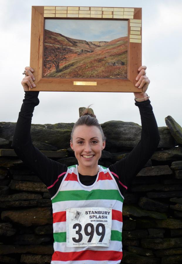 Keighley News: Helen Glover shows off her first-female trophy in the Stanbury Splash. Picture: Dave Woodhead