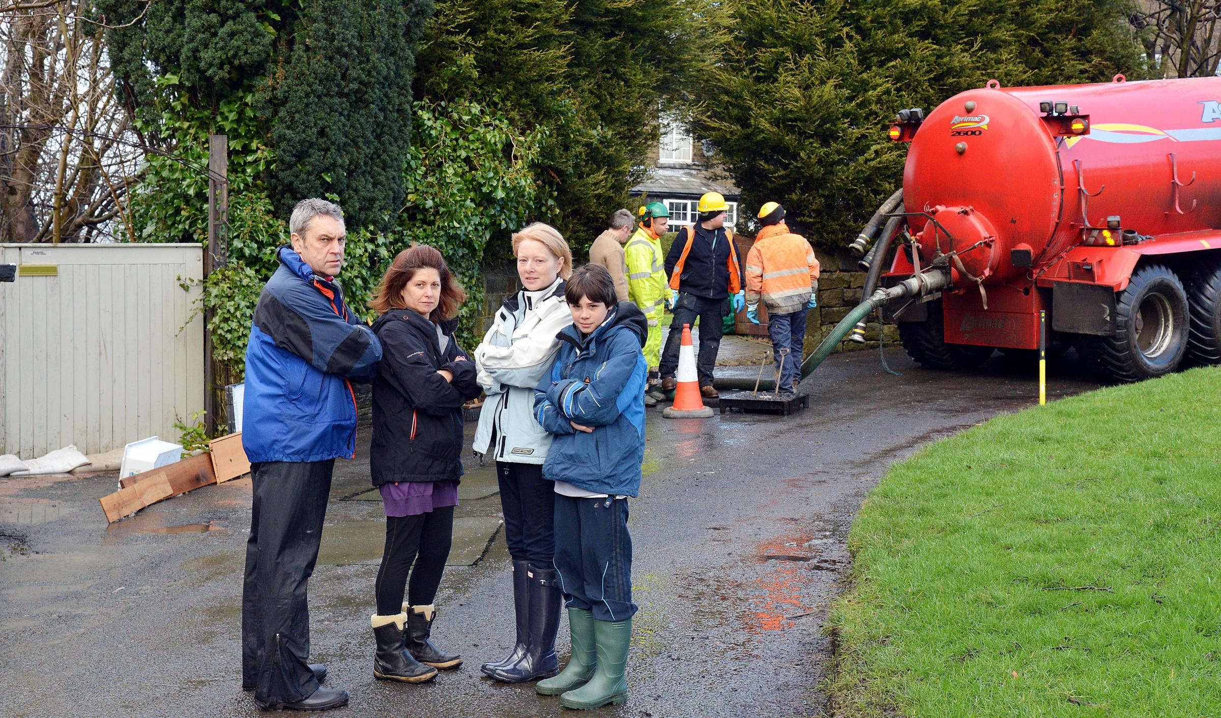Residents Ronnie Bagdonavicius,Caroline Bagdonavicius, Kate Wild, and Harrison Houldsworth wait as workmen clear the sewer