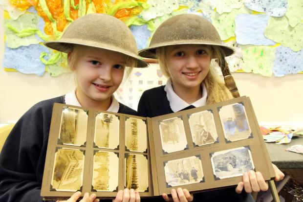 Steeton Primary School pupils Hannah Buchan, ten, left, and Hailey Spencer, 11, with Second World War items, including a photo album from Hailey's great-grandfather, James Holdsworth