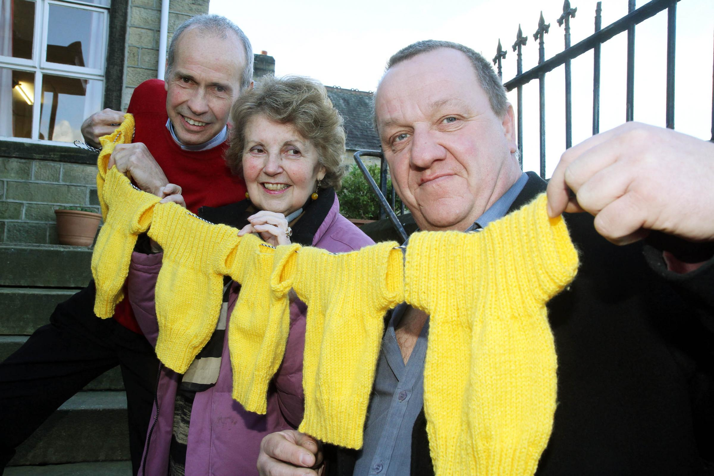 Silsden mayor Councillor Chris Atkinson shows off some of the knitted yellow jerseys with the Rev David Griffiths and St James's churchwarden Sheila Thompson