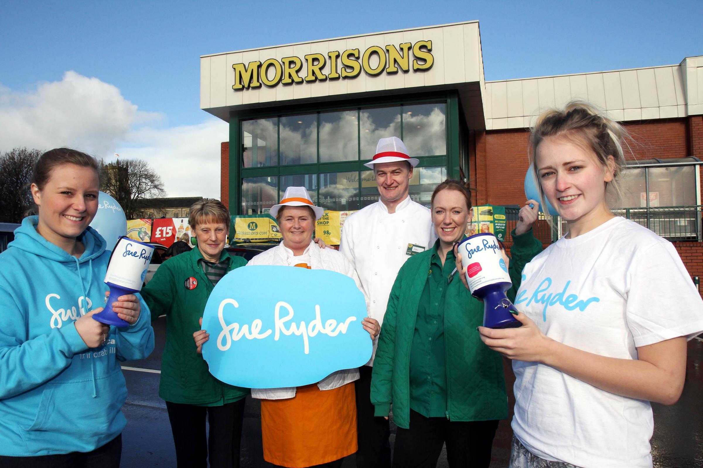 Manorlands fundraiser Hayley Ibbotson, left, and Poppy Holmes, right, who is on placement at the hospice, join Keighley Morrisons staff, from left, Jean Brown, Wendy Wiseman, Ian Burns and Tricia Cutts, to celebrate the partnership