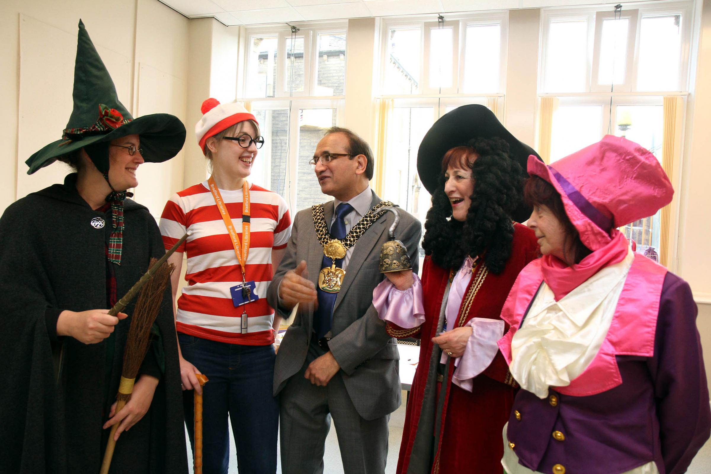 Lord Mayor of Bradford, Councillor Khadim Hussain, meets library staff, from left, Carole Birley, Frances Bancroft, Sally Haigh and Carol Wallace, who were  dressed as book characters for the reopening of Silsden Town Hall