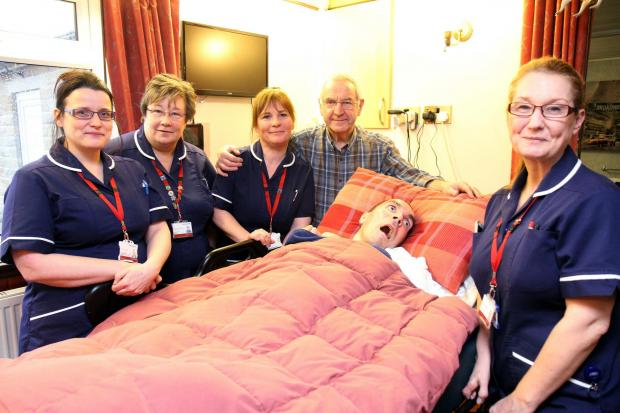Pictured last year: John Whitaker and his son Stewart Whitaker with the care team: from left, district nurse team leader Ruth Thomas; community staff nurses Alison Porteus and Johanne Corbett, and health care support worker Ellen Knowles