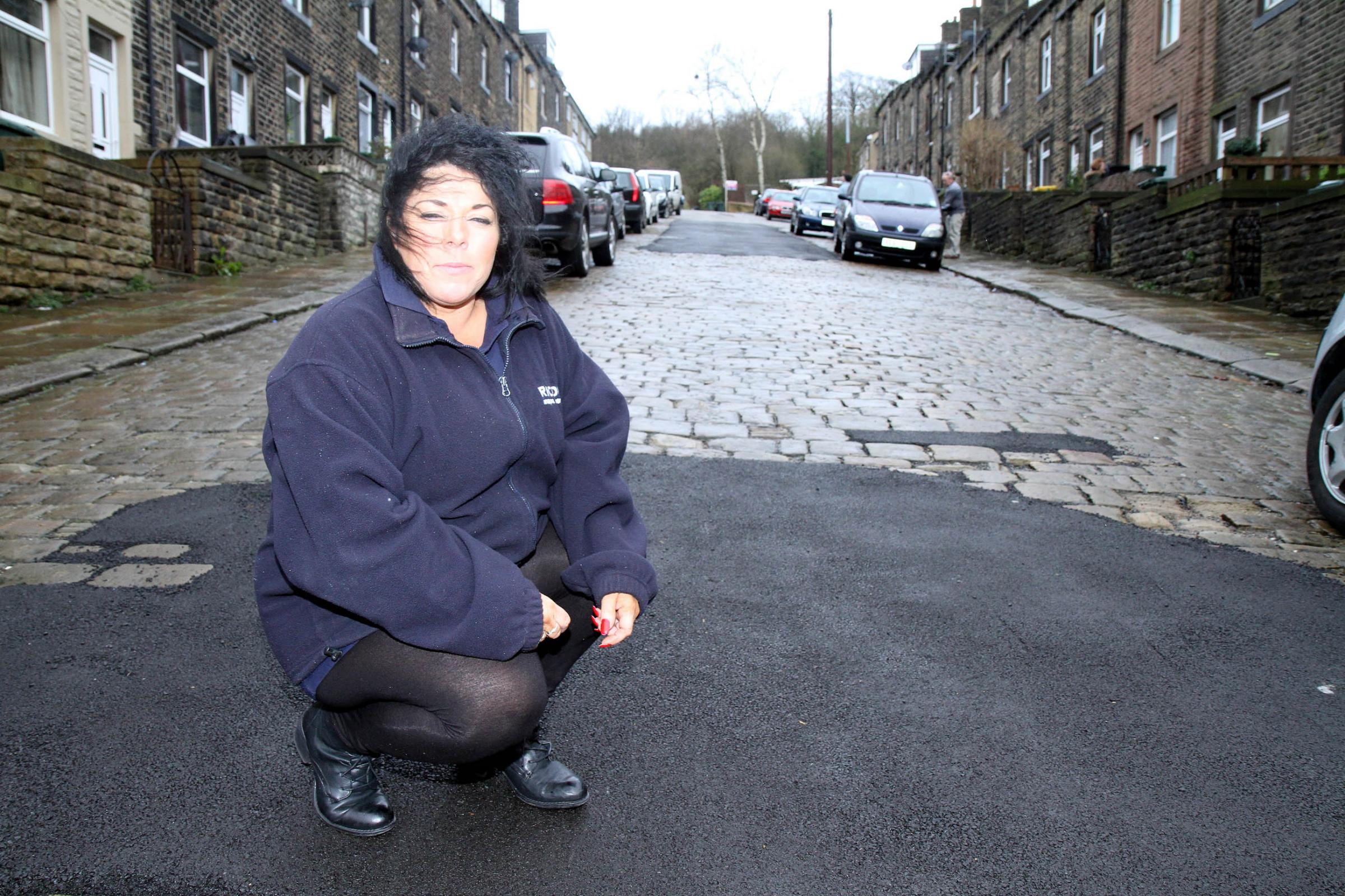 Carole Oksuz outside her Cliffe Terrace home in Keighley where asphalt has been used to repair historic damaged setts