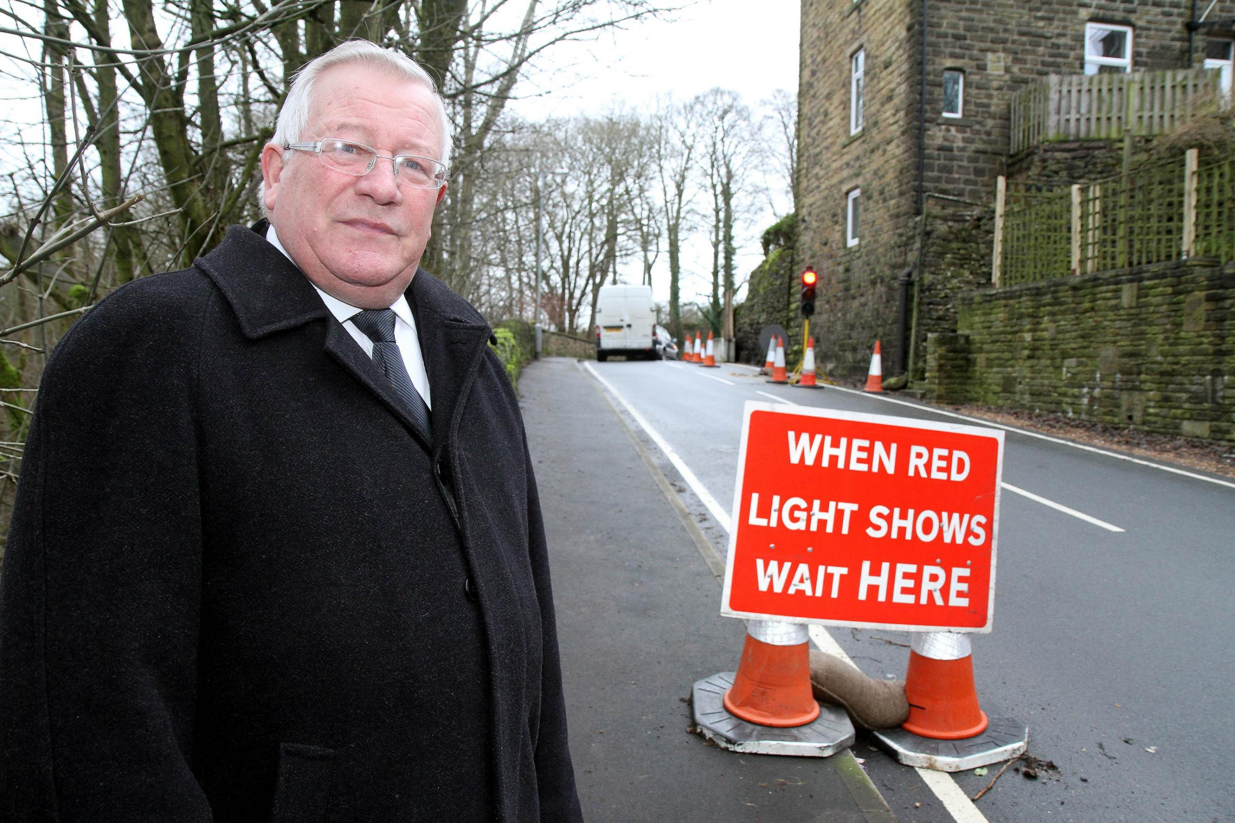 Councillor Mike Ellis stands at the site in Cullingworth where the road is due to close for works to be carried out