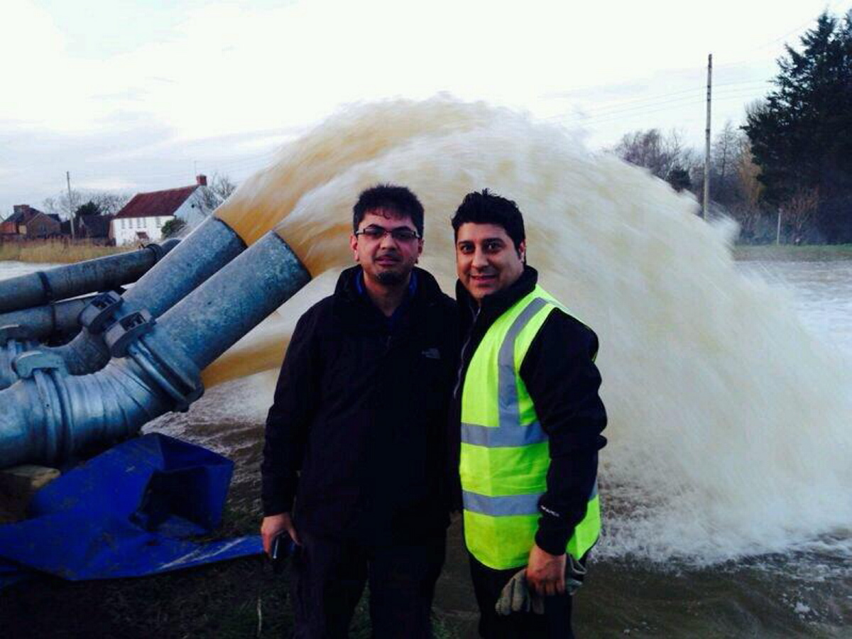 Dr Aziz Hafiz, left, and Ahmadiyya Muslim Association regional youth co-ordinator for the London region, Sheraz Ahmad, by pumps trying to clear water from flooded communities