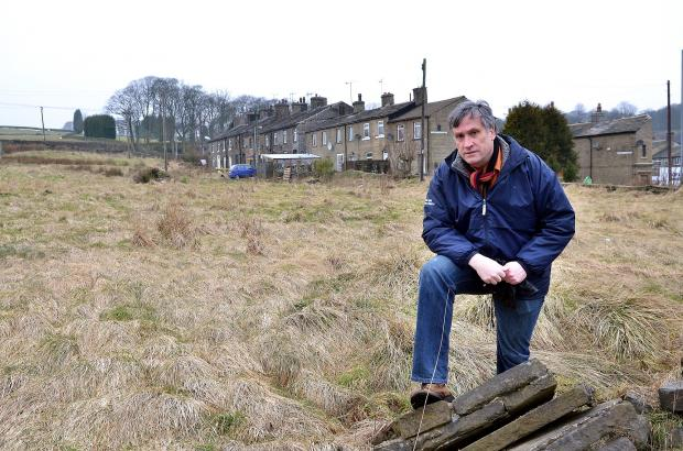 Keighley News: Councillor Simon Cooke in Denholme, where 35 homes are to be built on a field despite protesters' objections