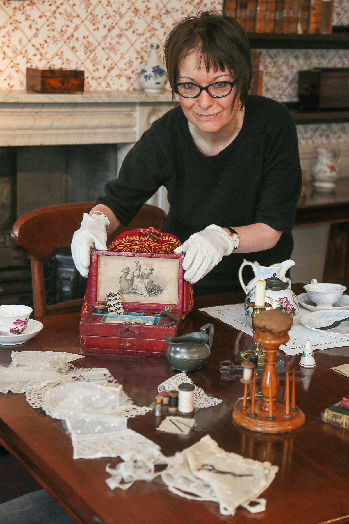 Ann Dinsdale gets gloved-up to help clean the delicate objects on display