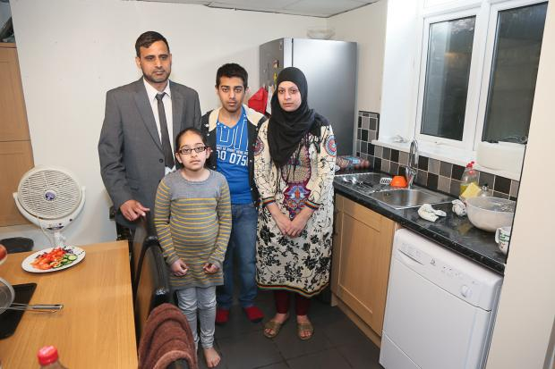 Keighley News: Councillor Khalid Choudhry, wife Shazia and children Qais and Husna in the kitchen of their Mannville Road home, which floods every time it rains