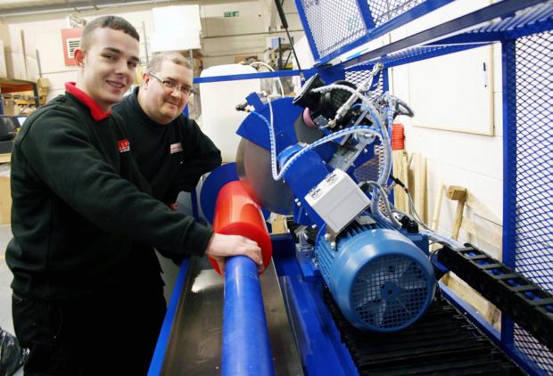 Keighley News: Viking's new apprentice Luke Summers, left, at work on the firm's new slitting machine under the guidance of Darren Milner